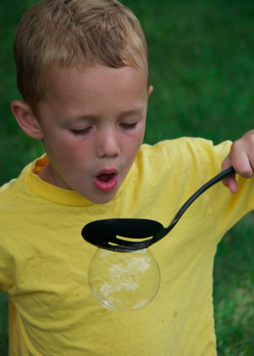 Blowing bubbles with a spoon.
