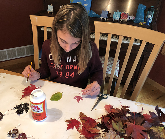 Charley painting leaves with Mod Podge